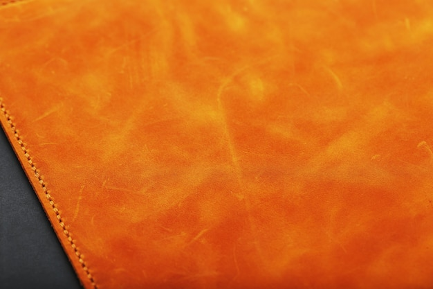 The leather cover of the album is made of brown handmade genuine leather . elements of a leather product close-up.