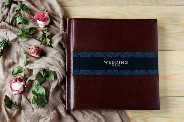 バラの花の装飾が施された革覆われた結婚式の写真アルバムのトップビュー