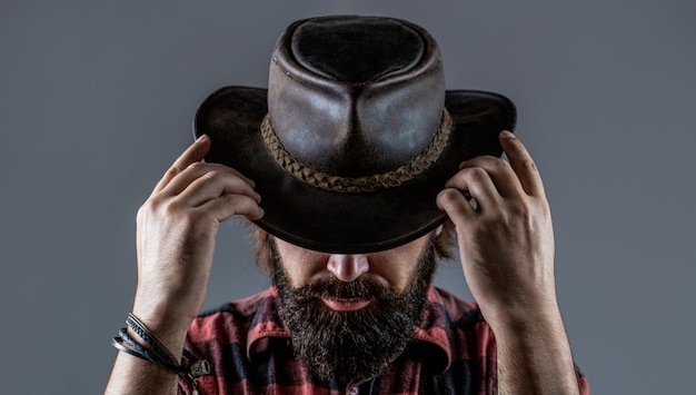 Leather cowboy hat. portrait of young man wearing cowboy hat. cowboys in hat. handsome bearded macho. man unshaven cowboys. american cowboy.