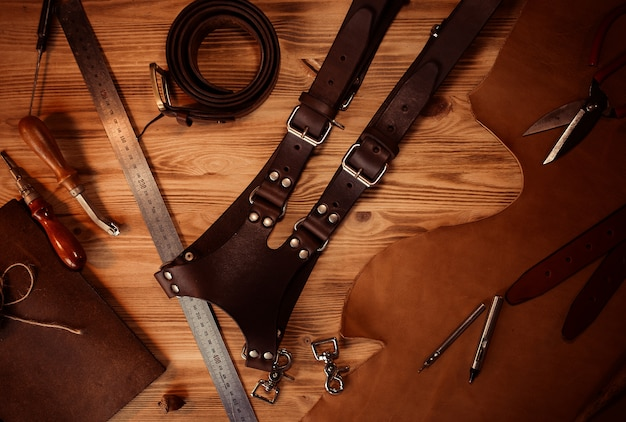 Leather craft and belt for photographers. tanner's tools on grey wooden background top view