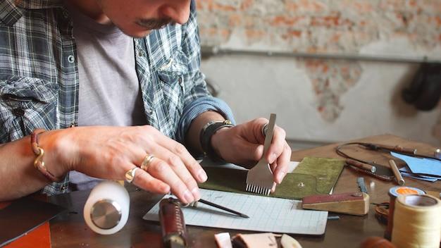Ремесленник из кожи делает кошелек, кошелек из куска натуральной кожи. ремесленник на своем рабочем месте с инструментами