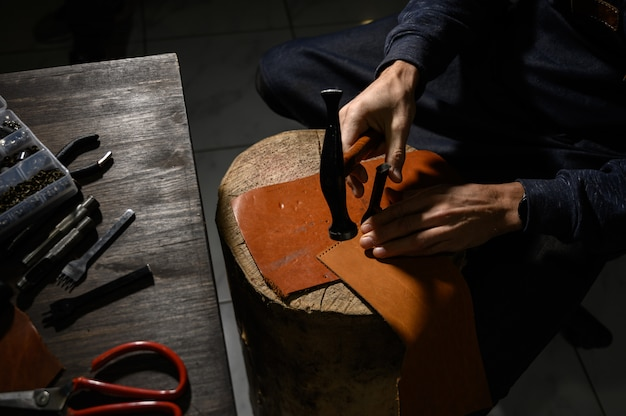 Leather craftsman works at the tanner shop