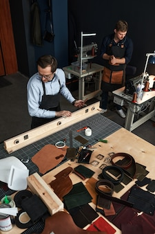 Leather craftsmen working making measupenets in patterns at table in workshop studio.