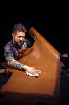 Leather currier는 직장에서 가죽 제품을 생산합니다.