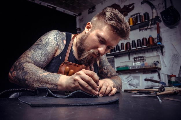 가죽 커터는 무두질 상점에서 새로운 가죽 제품을 만듭니다.