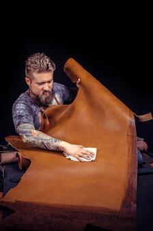 Закройщик кожи производит изделия из кожи в своей дубильной мастерской. дубильщик кожи, производящий кожгалантерею на рабочем месте.