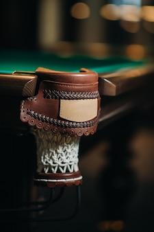 Leather decorative billiard hole and green table in the billiard club.