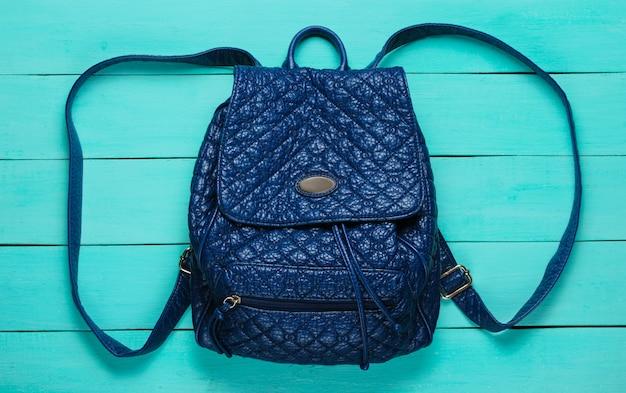 青い木製の表面にレザーファッションバックパック。