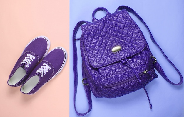 Leather fashionable backpack, sneakers on pastel background