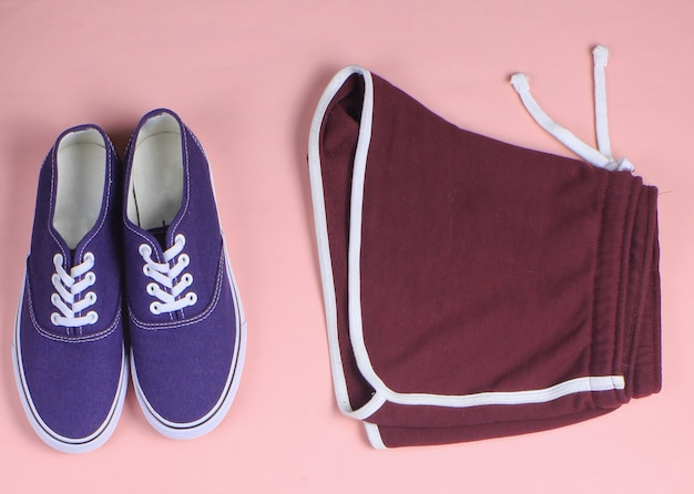 Leather fashionable backpack, sneakers, sport shorts on pastel background