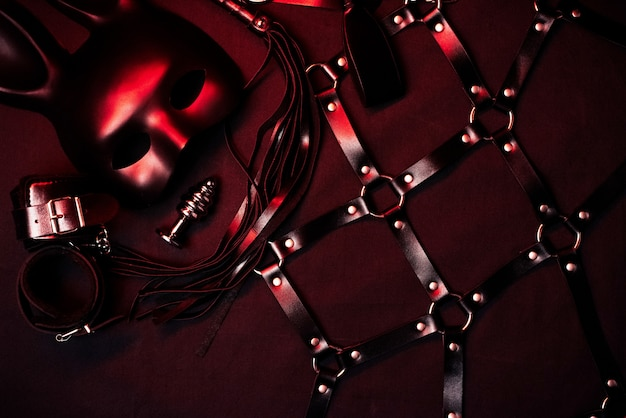 Leather flogger, handcuffs, belt, choker, mask and metal anal plug for bdsm