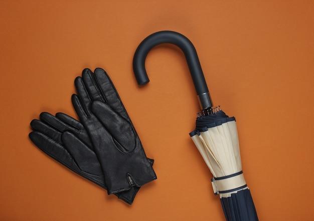 Кожаные перчатки и зонтик на коричневом