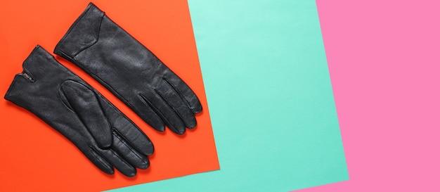 Кожаные перчатки на творческом цветном фоне. вид сверху. модный минимализм