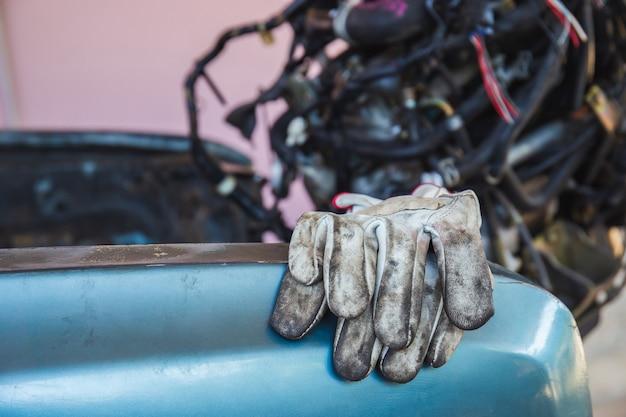 車のエンジンの背景がぼやけている車体シャーシフレームの革手袋