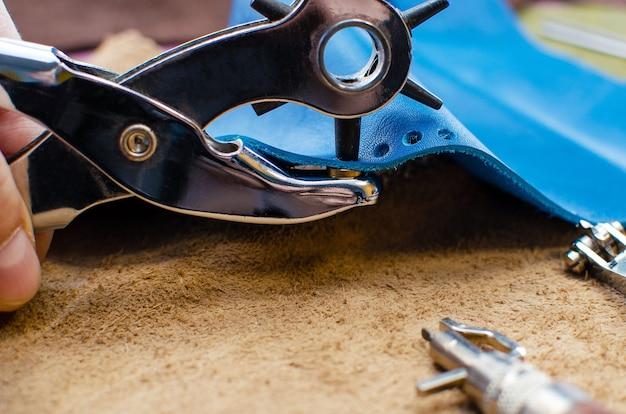 皮革製品の製造工程。バッグ、財布、クラッチを縫うためのツール。革の着色された部分。閉じる