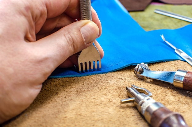 Leather goods manufacturing process. tools for sewing bags, wallets, clutches. colored pieces of leather. close-up