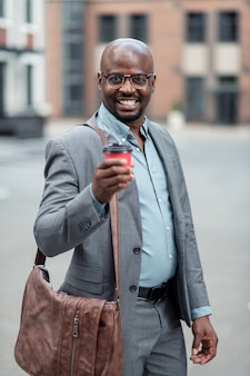 Leather hand bag. dark-skinned businessman with leather hand bag drinking morning coffee