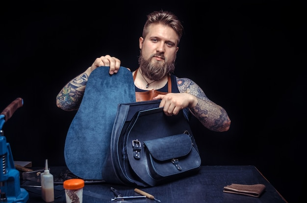 ワークショップで働く革製のハンドバッグ職人。