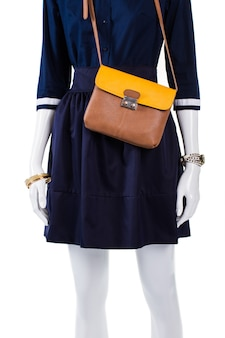 Leather handbag with navy shirt. mannequin wearing bicolor leather bag. lady's light-colored purse. dark navy outfit with accessories.