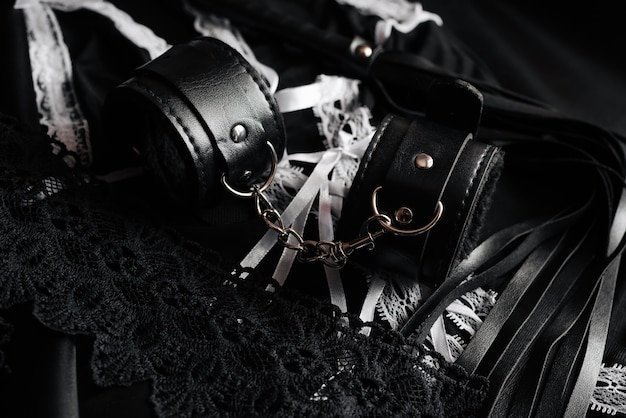 Leather handcuffs and whip for bdsm and maid costume for role-playing games