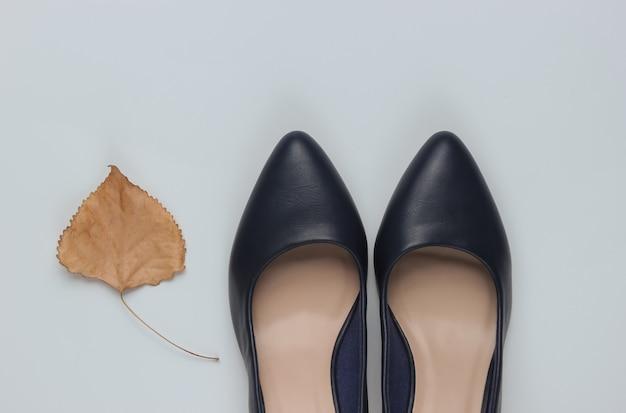 Кожаные туфли на высоком каблуке с сухим осенним листом на белой бумаге
