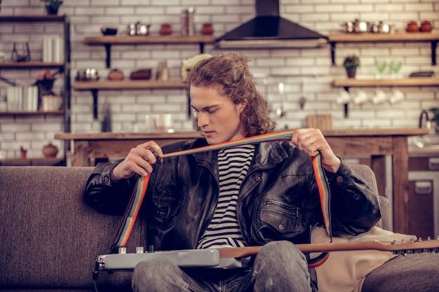 革のジャケット。彼のギターを保持している革のジャケットを着ている黒髪のスタイリッシュな才能のあるミュージシャン