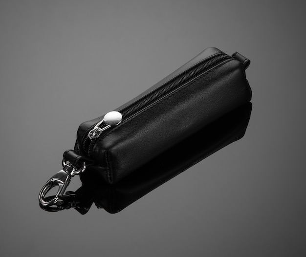 Leather key case with zipper on black background