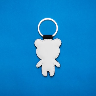 Leather key ring in bear shape on blue paper background
