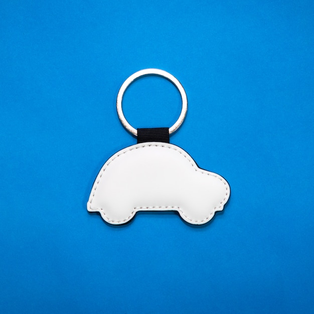 Leather key ring in car shape on blue paper background