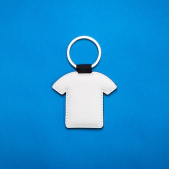 Leather key ring in shirt shape on blue paper background