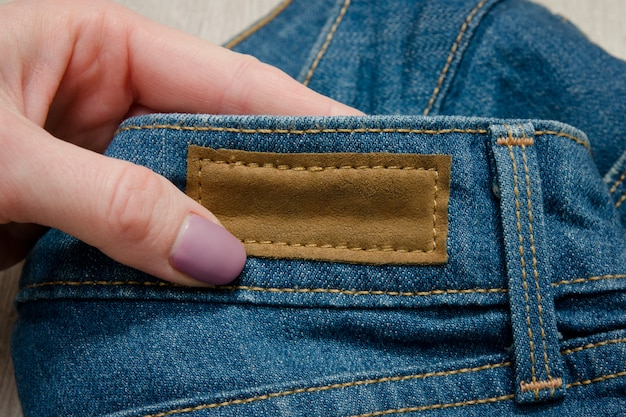 Leather label on jeans in female hand