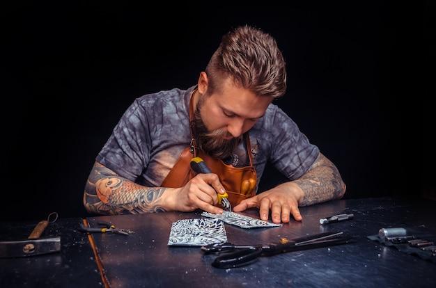 Кожаный мужчина производит новый продукт из кожи