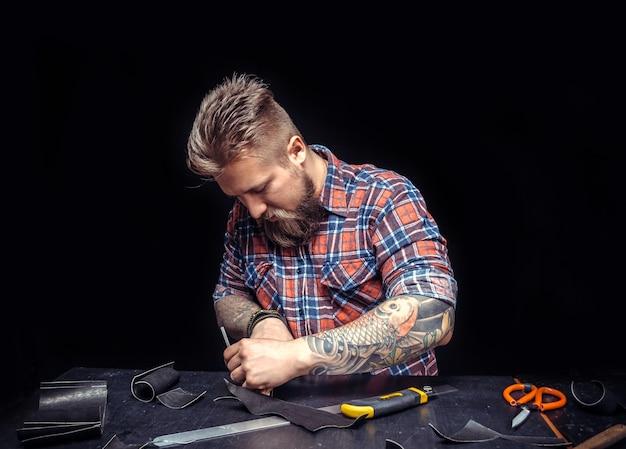 Кожаный мужчина обрабатывает кожаную заготовку на рабочем месте