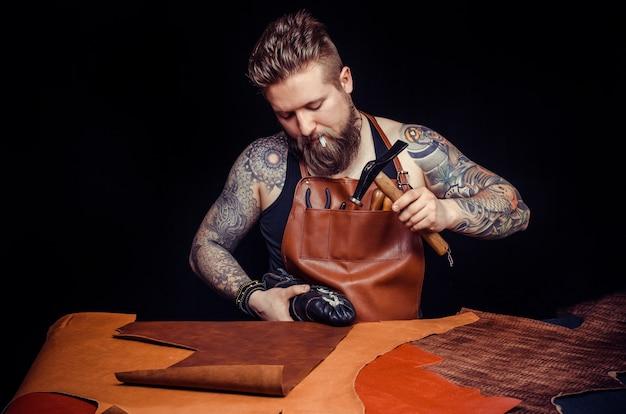 Кожаный мастер изготавливает новинки из кожи в кожевенном магазине.