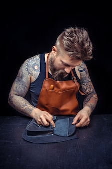 Leather master works as an artisan at his workshelf.