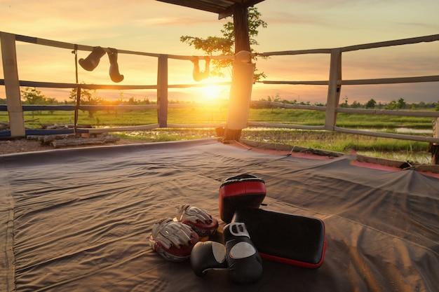 Кожаная перчатка, размещенная на полотне ринга в лагере тренировочного боксера, используется для тренировок по тайскому боксу, кик-боксу и смешанным единоборствам. гимназия тайского бокса закрыта из-за пандемии covid 19.