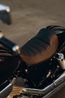 가죽 오토바이 좌석, 클로즈업. 크롬 디테일이 있는 세련된 맞춤형 초퍼 모토바이크. 부드러운 선택적 초점입니다.