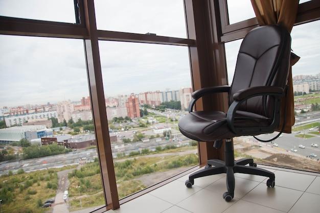 Кожаное офисное кресло на стеклянном балконе с панорамным видом на большой город или мегаполис. концепция работы на дому или безработицы. авторское право для сайта или баннера
