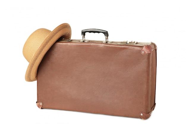 Кожаный старый чемодан при шляпа изолированная на белизне. концепция путешествия