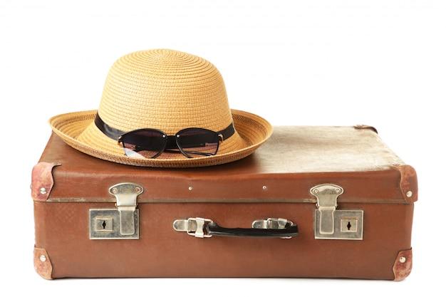 Кожаный старый чемодан с изолированной шляпой. концепция путешествия