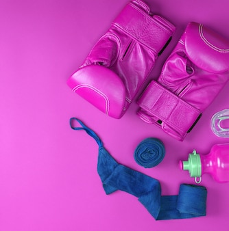 Leather pink boxing gloves, a blue textile bandage
