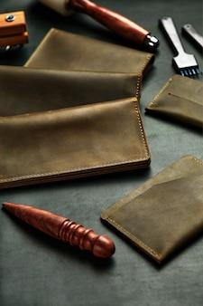 Кожаные изделия раскладываются на мастерском столе, на куске кожи среди инструментов, кожаной фурнитуре ручной работы, кожаных кошельках такого же цвета.