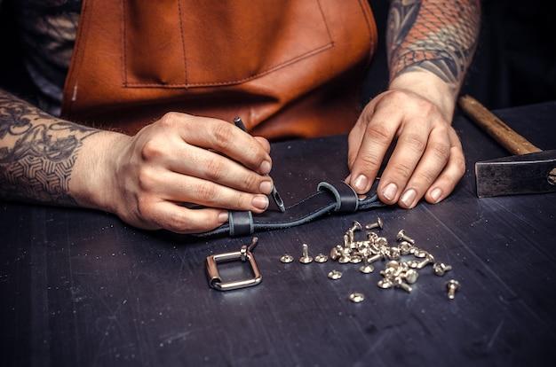 Leather professional создает новые изделия из кожи в своей студии.