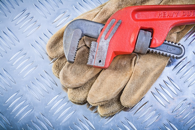 Leather protective gloves monkey wrench on corrugated metal