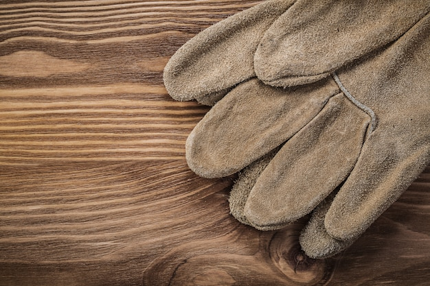Leather protective gloves on vintage wood board construction concept