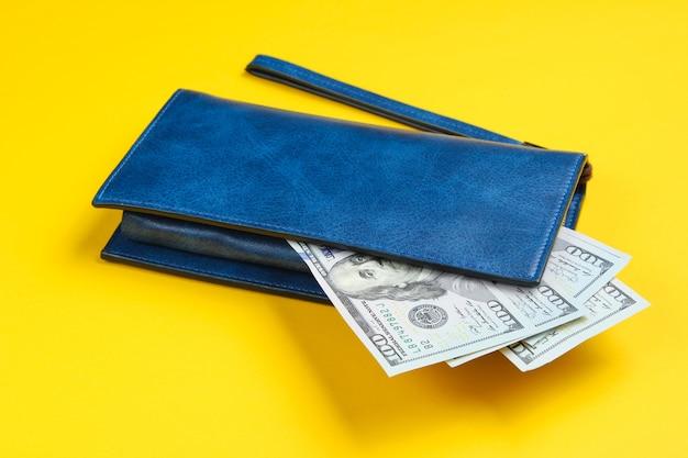 黄色の革の財布と100ドル札。