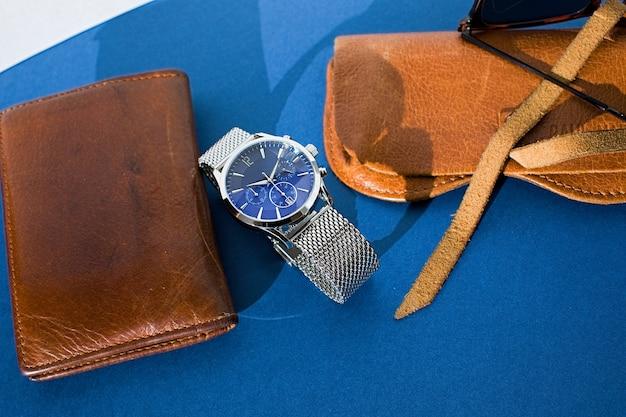 革製の財布、金属のブレスレット、サングラス、青の背景にノートパソコンで見る。男性用アクセサリー。上面図