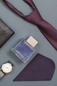 Кожаный кошелек, часы с ремешком, мужской одеколон, носовой платок и галстук на сером фоне.