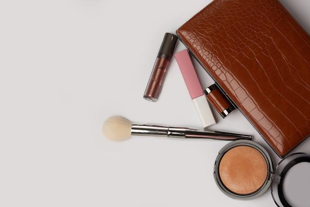 ブロンズパウダー、リップグロス、グレーの背景にブラシをかけた革製の財布。空きスペース
