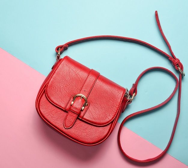 Leather red female bag on a pink blue pastel background. top view.